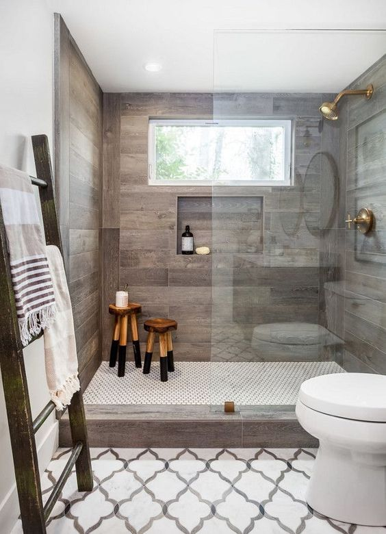 an elegant shower space with wood-looking tiles on the walls and a built-in shelf