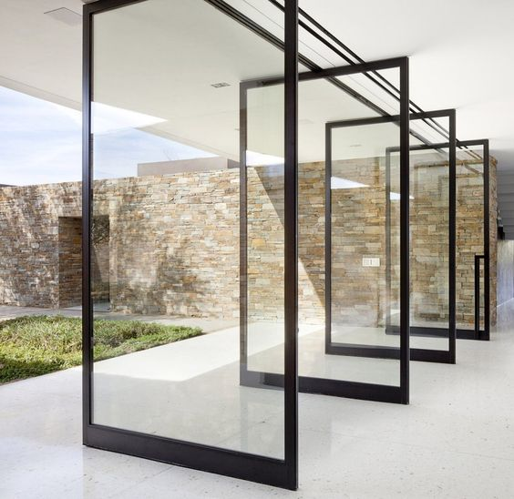 the whole wall is made of pivot doors, which create a strong indoor-outdoor connection