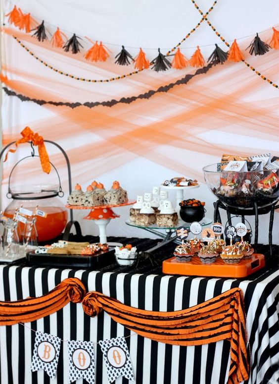 a bold orange, white and black Halloween dessert table with a striped tablecloth, banners all over