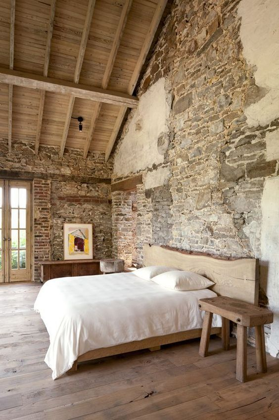a rustic attic bedroom with rough stone walls, a woode floor and wooden furniture
