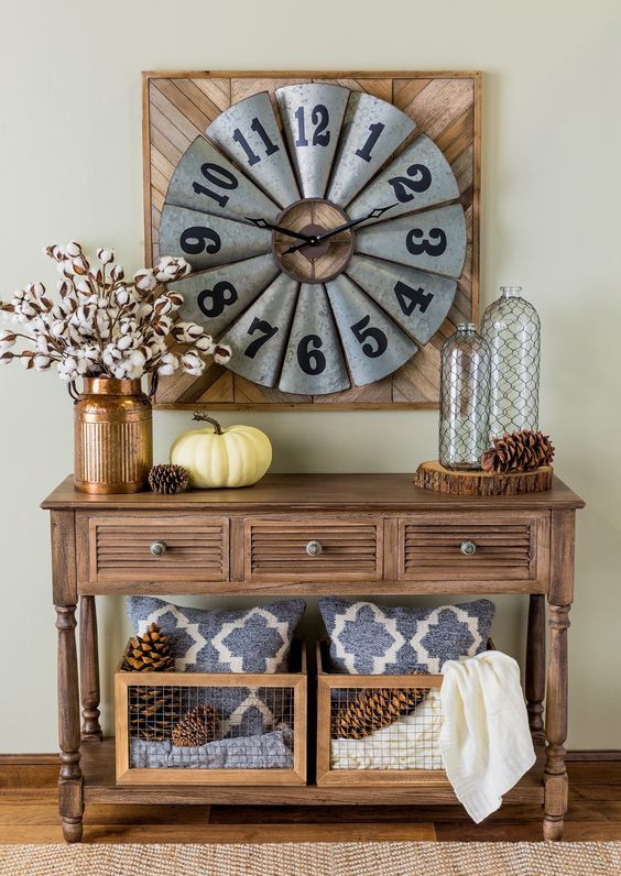 a vintage wooden console table with large pinecones, cotton branches in a copper vase and wooden crates with pinecones