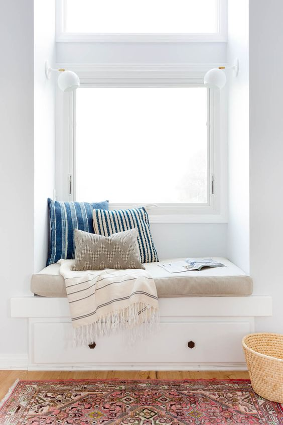 a window seat with a blanket and pillows is ideal for reading