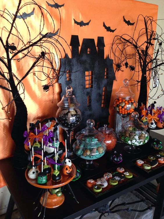 a haunted dessert table with a black house, bats, trees and lots of themed desserts
