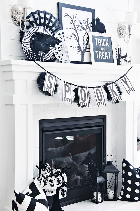 a modern black and white Halloween mantel with a banner, wreaths and lots of different stuff