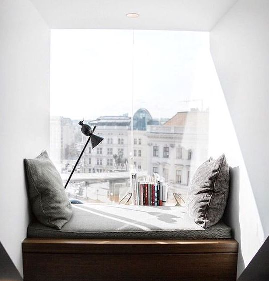 a modern window seat reading nook with cushions and pillows and an additional lamp