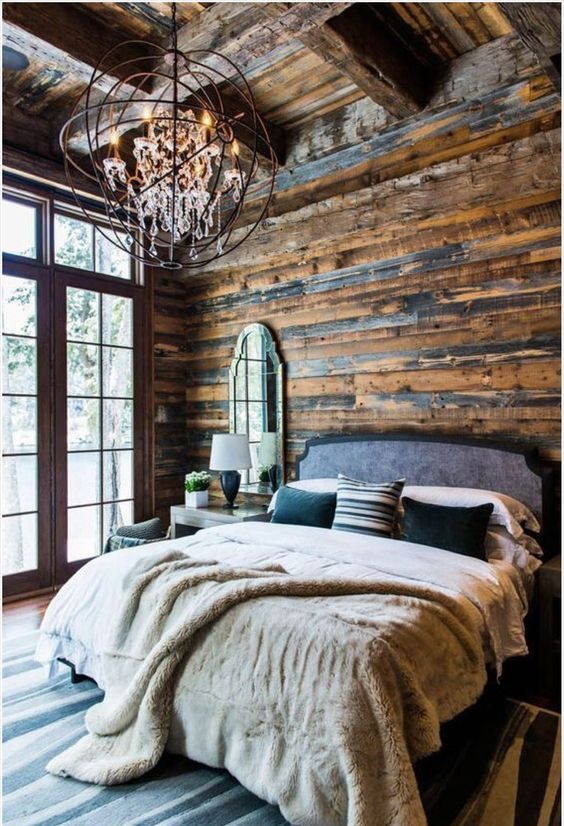 a rustic and chalet-inspired retreat with walls and ceiling covered with reclaimed wood and a metal chandelier