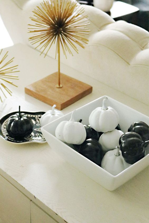 a simple black and white pumpkin display in a dish is a timeless idea