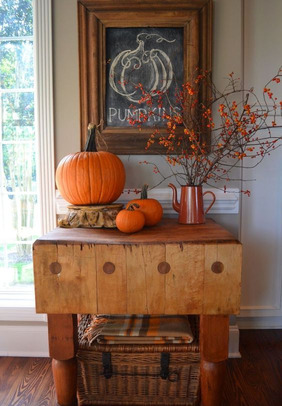 an entryway console with orange pumpkins, some branches with berries and a wicker chest