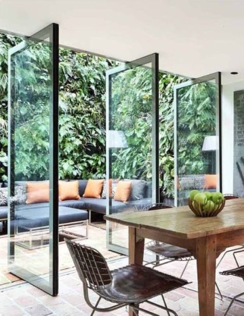 pivoting glass doors connects the indoor dining area and outdoor living room