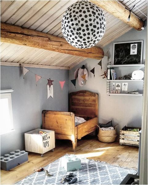 the rustic look is achieved with wooden beams and a wood kid's bed, which echo with the wooden floor
