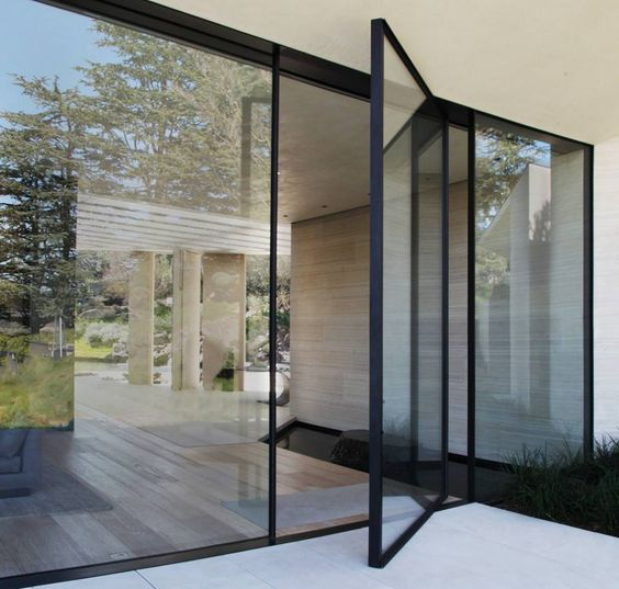 a modern black framed pivot glass door is a gorgeous idea to emphasize the entry