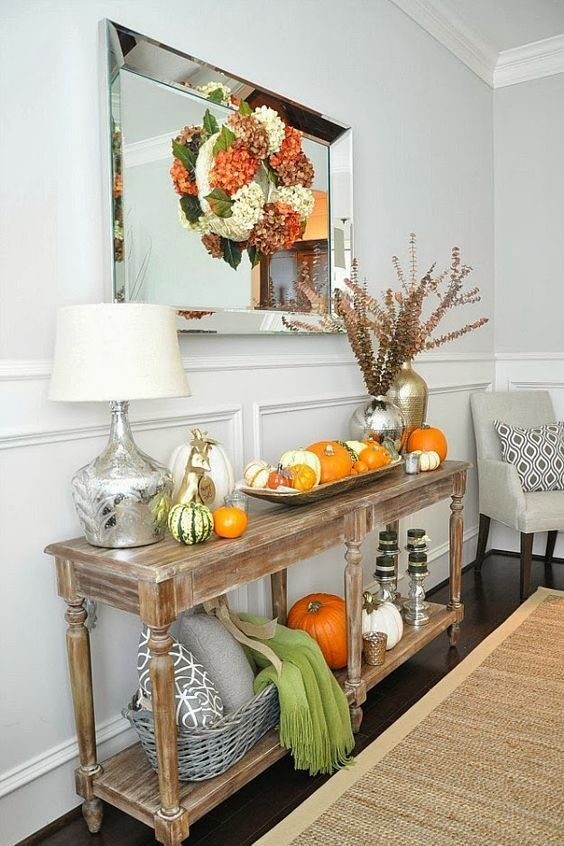 a rustic console table with pumpkins on display and a colorful fall wreath over it