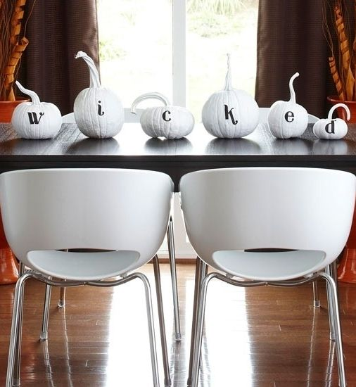 a white pumpkin display with black letters look bold, modenr and chic