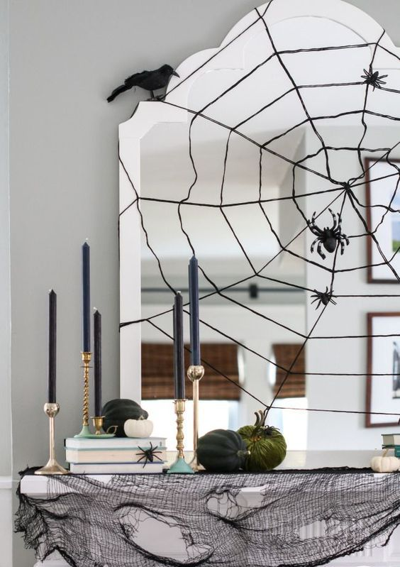 modern Halloween mantle with a spider web mirror, ravens and goldcandle sticks, black cheesecloth to cover the mantel