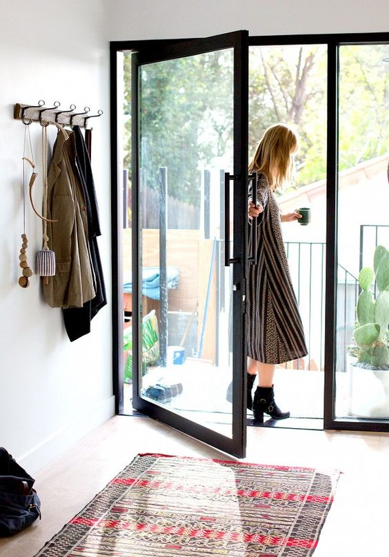 a chic black frame glass pivot door makes the entryway more eye-catching and bold