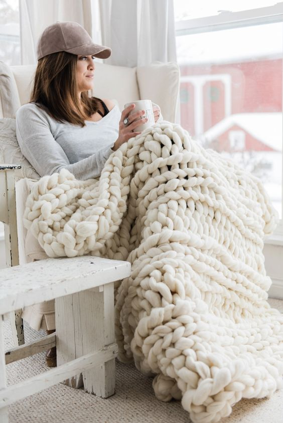 a chunky knit wool ivory-colored blanket is amazing for indoor and outdoor cuddling
