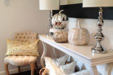 06 a console table with various shiny pumpkins and a wicker basket with pillows and faux fur