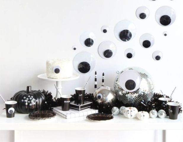 a fun black and white Halloween dessert table with lots of googly eyes everywhere