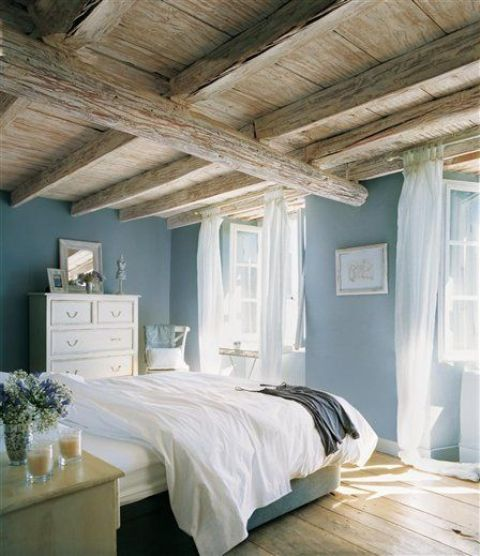 a gorgeous wood ceiling with beams and wood floors create a stunning pastel space