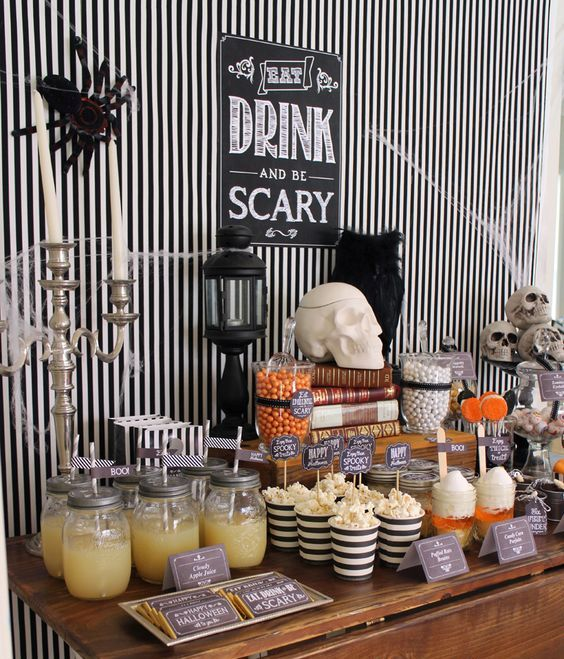 a simple stylish dessert table decor with black and white stripes, vintage candle holders and skulls