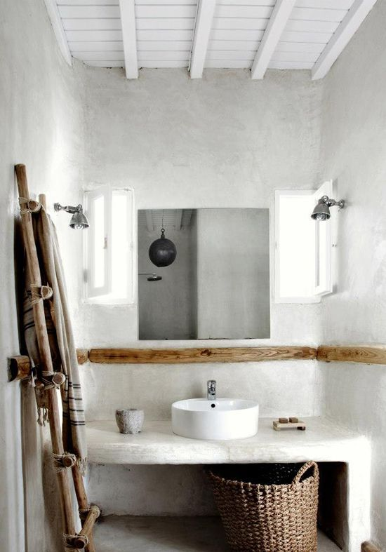 a coastal bathroom is given a spa feel with stucco walls and natural wood