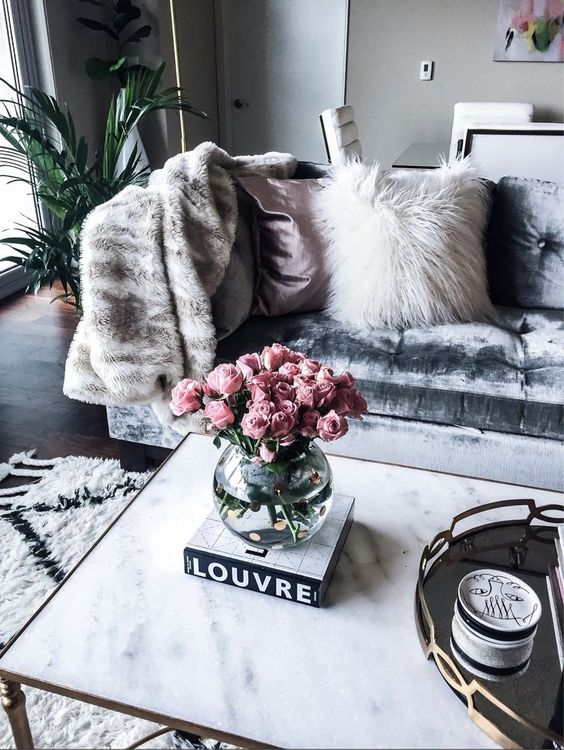 a neutral faux fur blanket and a pillow of a different texture for a glam feel