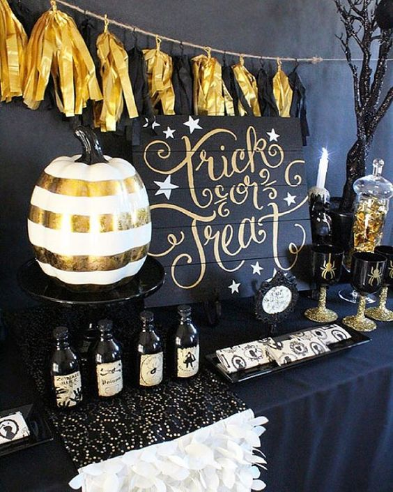 a stylish black and gold dessert table with a banner, a calligraphy sign and skulls
