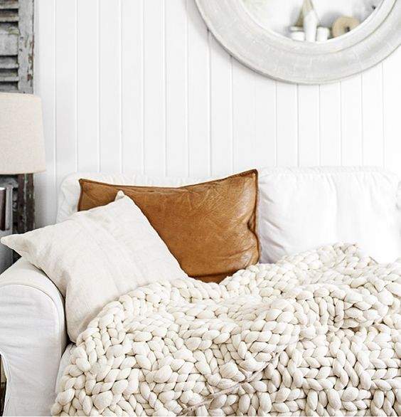 a white chunky knit blanket and a leather pillow make this sofa super stylish
