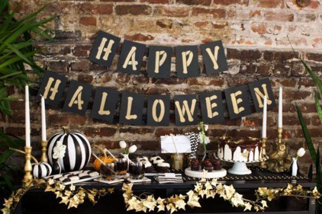 a chic Halloween table in black, white and gold, with a leaf garland and a striped pumpkin