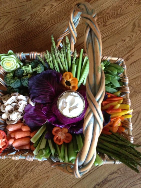 a chic and cozy rustic veggie basket with a dip in a small bowl in the center