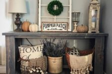 08 a console with various faux pumpkins, lavender and pillows in baskets