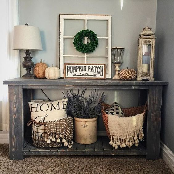 a console with various faux pumpkins, lavender and pillows in baskets