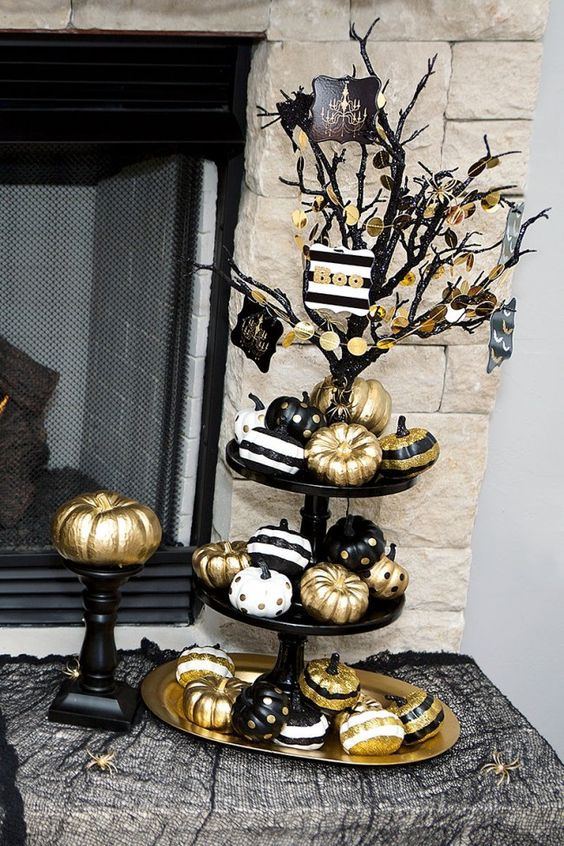 a stand with black, gold and white pumpkins with stripes and polka dots looks cute and glam