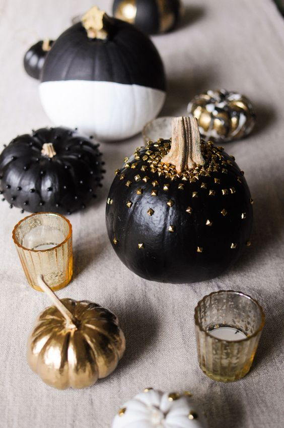 black, white and gold pumpkins decorated with spikes, beads and gold touches on the table
