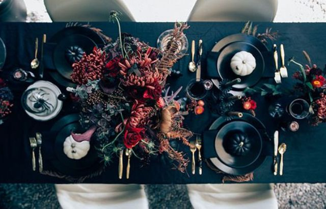 elegant moody Halloween tablescape with dark florals, black and white pumpkins and black matte plates