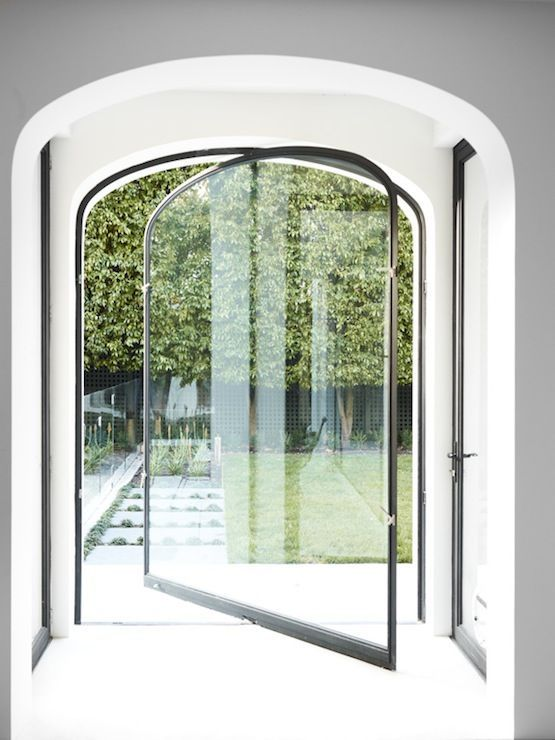this oversized pivot door seems a seamless glass wall that brings much light in