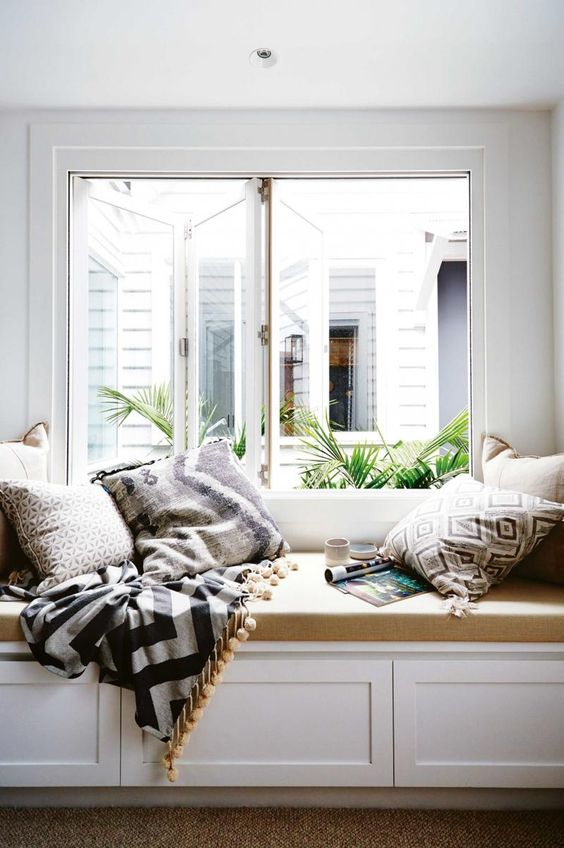 upholstered window seat with pillows and a blanket is a comfy space