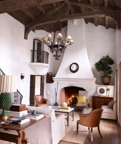 a Spanish colonial style living room with stucco walls and a stucco fireplace looks very elegant