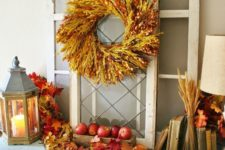 09 a console table with fall apples, leaves, wheat spikes, a spike wreath and some pumpkins under the table