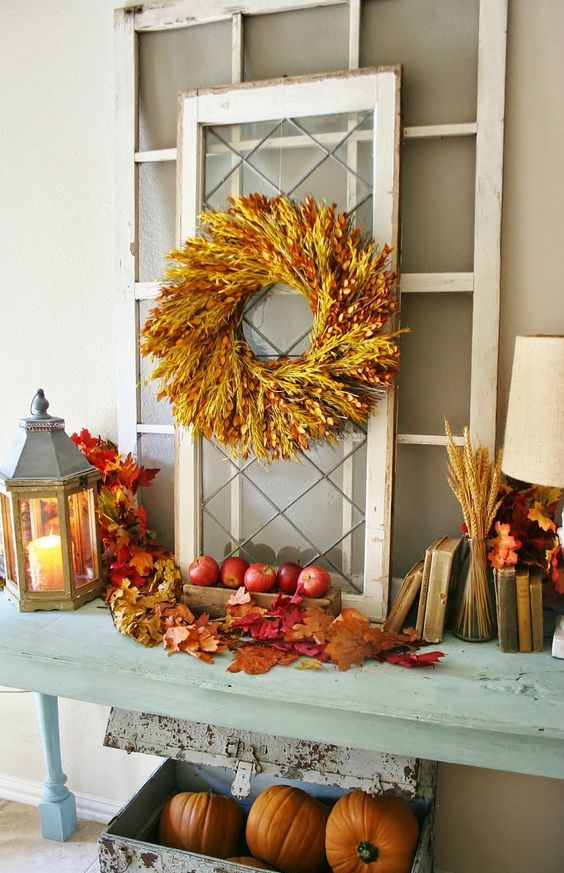 a console table with fall apples, leaves, wheat spikes, a spike wreath and some pumpkins under the table
