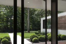 09 a glass wall with a pivot door makes an impression of having no boundaries with outdoors