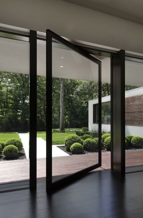 a glass wall with a pivot door makes an impression of having no boundaries with outdoors
