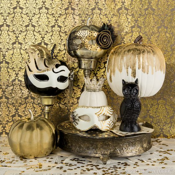 a stylish combo of black, white and gold pumpkins with masks for a refined party