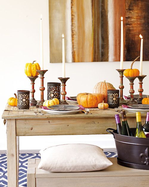 natural pumpkins placed on the table and small vintage stands add a fall flavor to the table