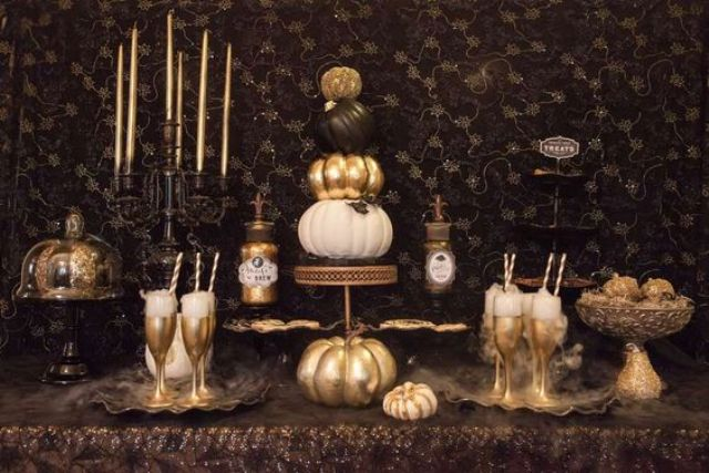 refined gold and black vintage Halloween dessert table with candles and gold goblets