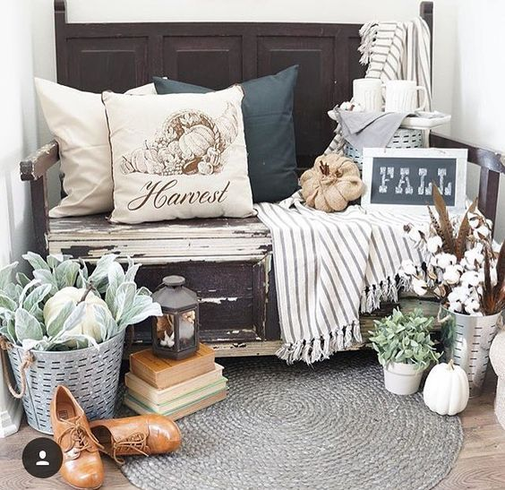 a bench with burlap pumpkins, a bucket with feathers and cotton, a bucket with veggies