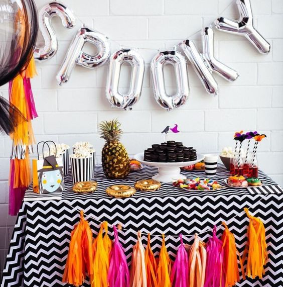 a cheerful beach-inspired dessert table with silver letter balloons and a colorful tassel garland