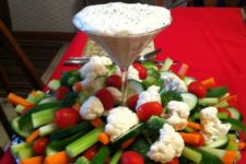 10 a chic veggie tray with a dip in a martini glass and vegetables all around