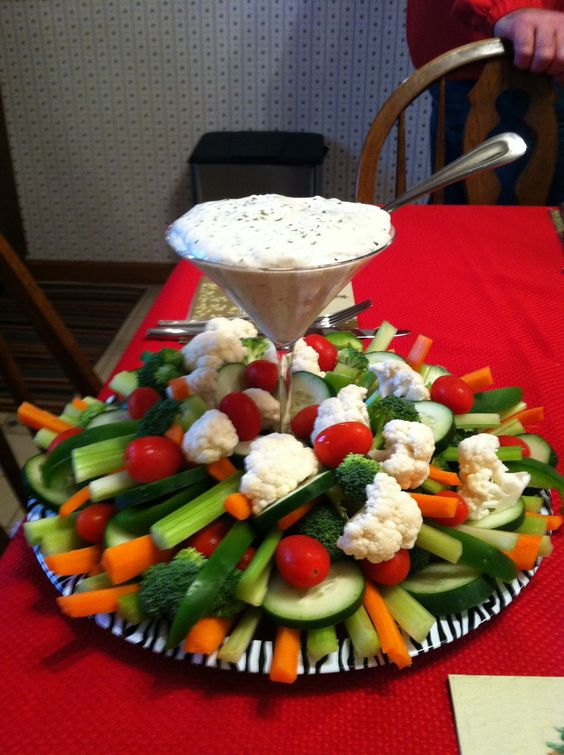 a chic veggie tray with a dip in a martini glass and vegetables all around