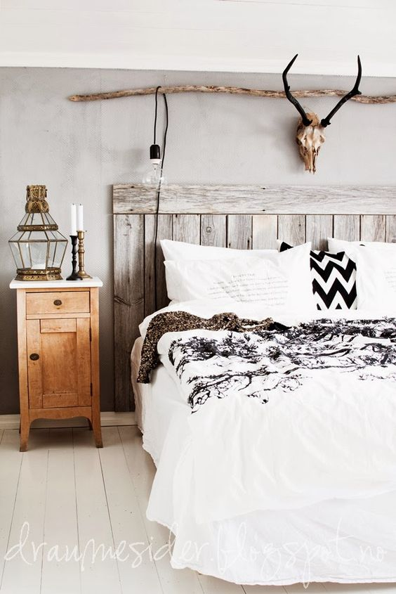 a whitewashed wood headboard, a branch and a skull and a wood nightstand for a rustic feel